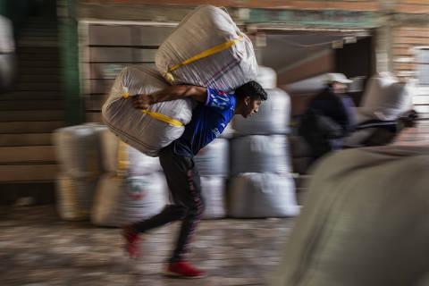 Carregador leva sacos de folha de coca no mercado Villa Fatima, em La Paz