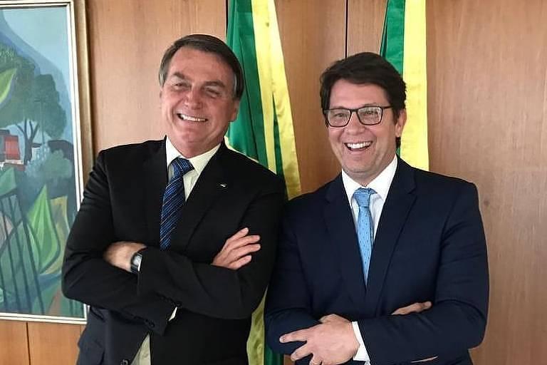 Dois homens brancos lado a lado sorrindo, em frente à faixa presidencial