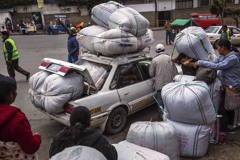 Cocaleiros carregam sacos de folha de coca do lado de fora do mercado de Villa Fatima, na capital La Paz
