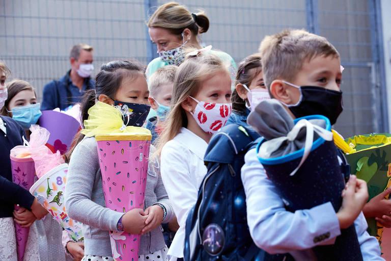 Fila de crianças usando máscaras coloridas