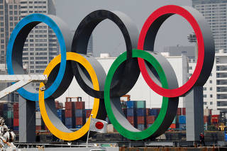 FILE PHOTO: The giant Olympic rings, which are being temporarily removed for maintenance, are seen behind Japan's national flag, at the waterfront area at Odaiba Marine Park in Tokyo