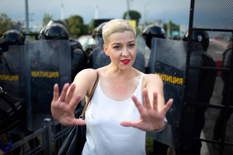 Moça loira de cabelos curtos e camiseta regata branca estende os dois braços para a frente com as mãos espalmadas, tendo às costas uma fileira de soldados de capacete e escudos