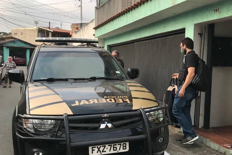 Viatura da Polícia Federal em frente a uma casa verde com portão cinza