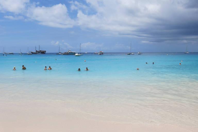 Praia com água azul e areia branca, com pessoas na água