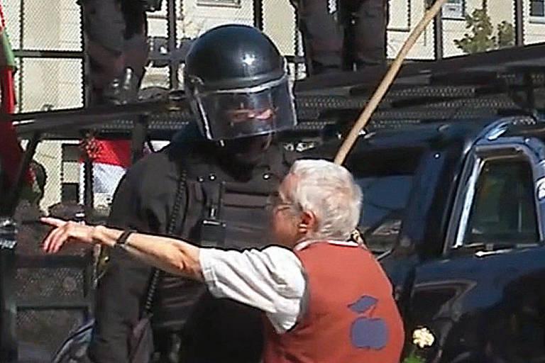 Dois policiais de capacete olham para uma senhora de blusa branca e colete vermelho, que gesticula