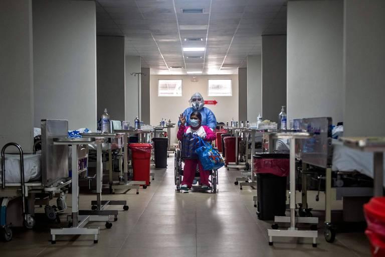 Profissionais de saúde empurra cadeira de rodas com paciente recuperado da Covid-19 em hospital em Lima, no Peru
