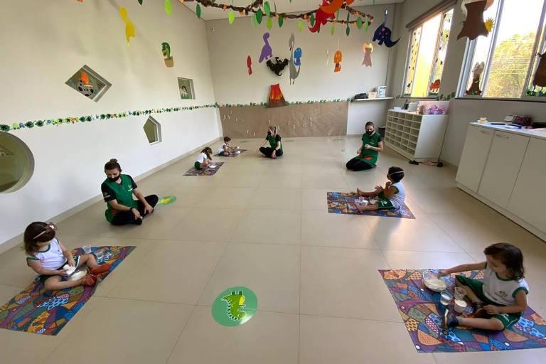 Seis crianças estão sentadas em tapetes, com um professor, em uma sala. Elas estão distantes umas das outras.