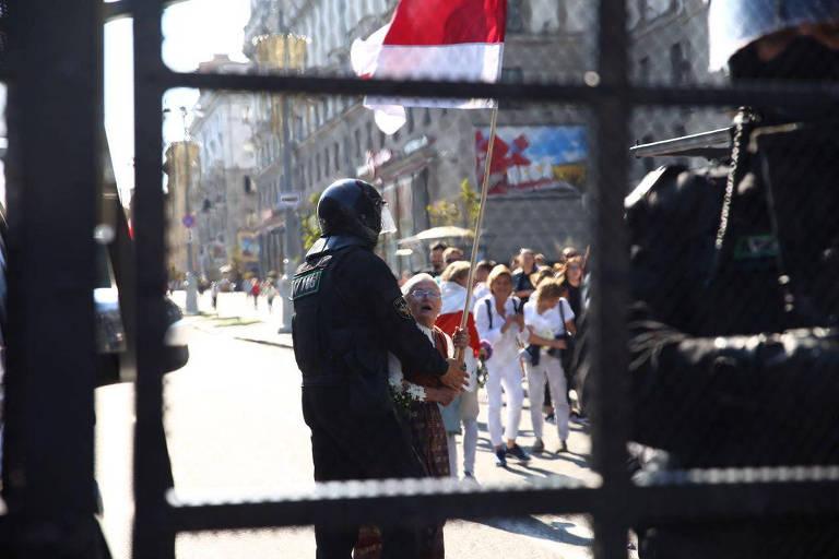 Em foto tirada através de uma grade, é possível ver um policial seguranda a idosa.