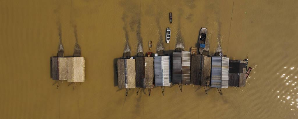 Balsas de garimpo de ouro operam ilegalmente no rio Madeira em frente a cidade de Humaitá, no sul do Amazonas; foto aérea mostra as balsas, que são como casinhas, liberando um rastro sujo na água marrom do Madeira