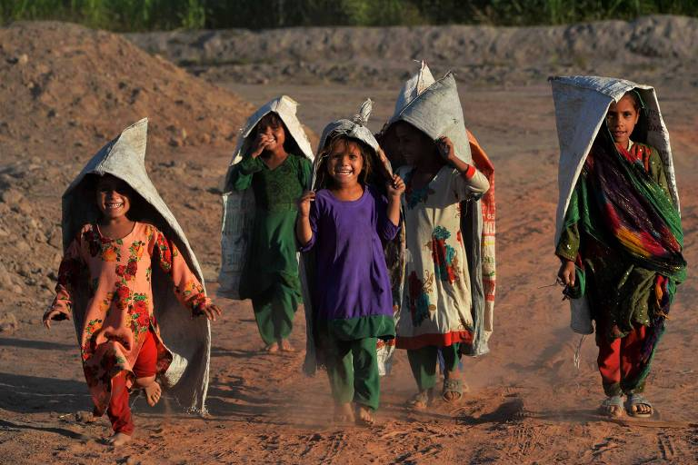 grupo de cinco crianças com roupas coloridas e sacos na cabeça