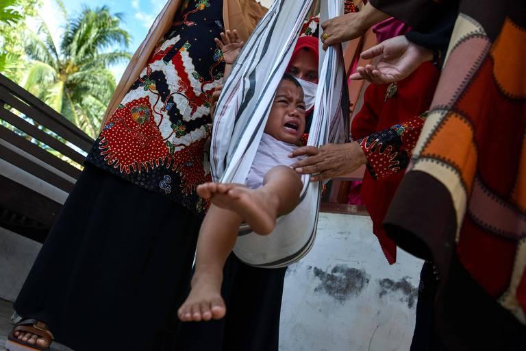 criança pendurada em faixa de pano presa a balança