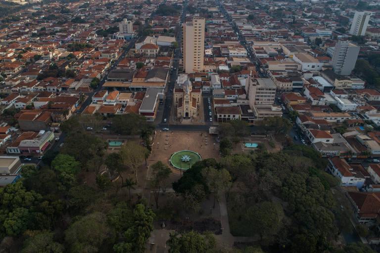 imagem de drone mostra praça com igreja ao lado