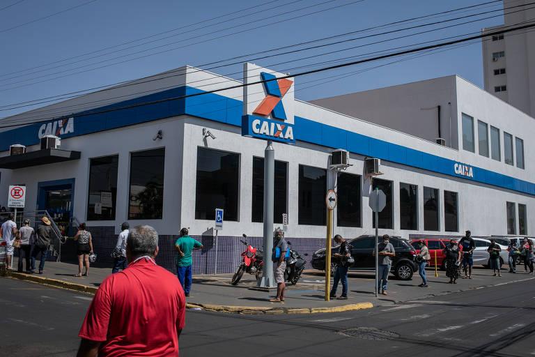 Fila na porta da Caixa em agência do centro de Jaboticabal para sacar benefício emergencial do Governo Federal; banco pretende demitir 7.200 funcionários