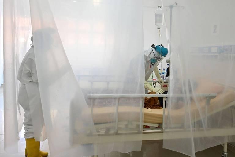 Foto mostra uma cama de lado com paciente de Covid-19 e dois profissionais, em pé, tratando o doente. Na frente, há uma cortina opaca