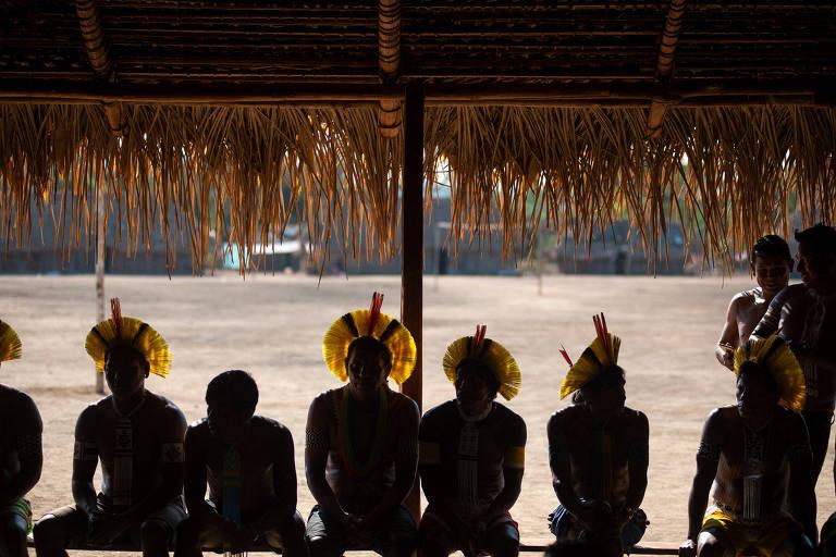 Indígenas, alguns de cocar, aparecem em imagem contra a luz