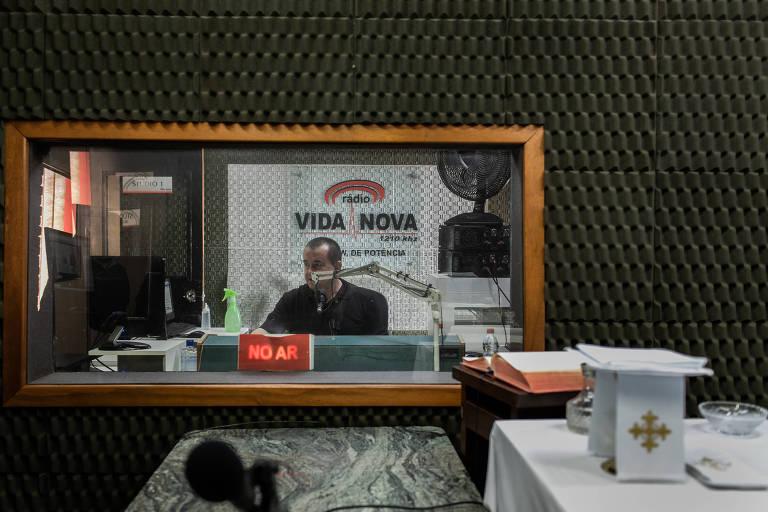 homem sentado fala ao microfone em estúdio de rádio