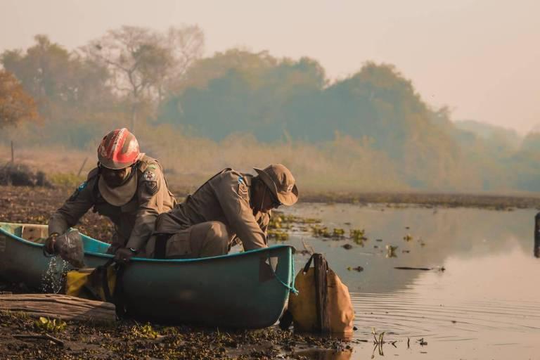 Dois bombeiros de dentro de um barco em um rio no Pantanal. Ao fundo, o por do sol.