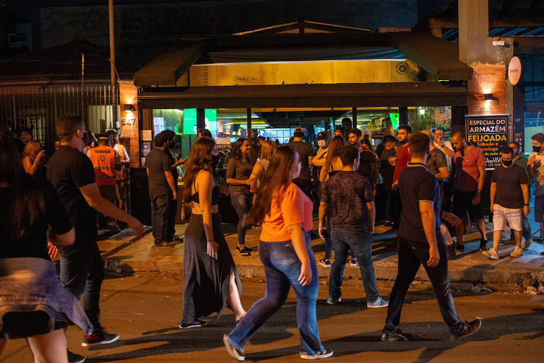pequena multidão de pessoas parada diante de estabelecimento com toldo durante a noite