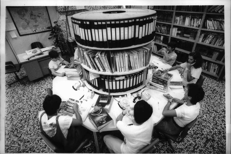 Jornalistas sentados em mesa circular atendem a telefonemas no serviço Folha Informações. Foto em preto e branco de 1986