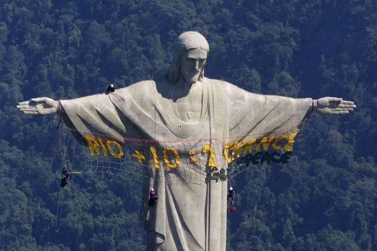 "foto aérea que mostra alpinistas escalando a estátua do cristo redentor e estendendo a faixa de protesto Rio + 10 = Segunda chance?"" com letreiro amarelo nos braços abertos do cristo"