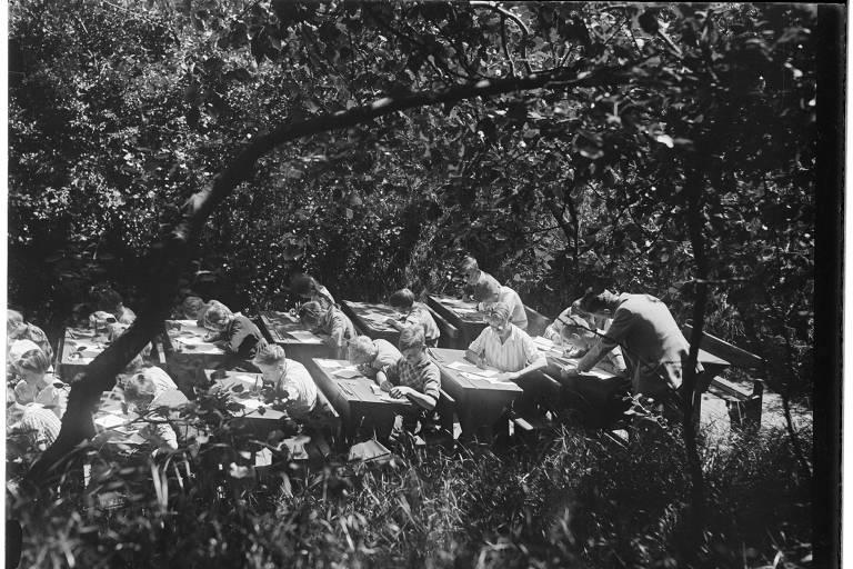 Escola a céu aberto na Holanda, por volta de 1935, em foto de autor desconhecido; imagem em preto e branco mostra alunos em carteiras ao ar livre, cercados de árvores, com um professor