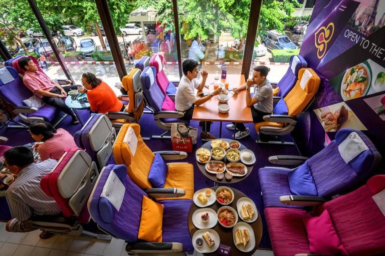 As pessoas se sentam em assentos de avião enquanto jantam em um restaurante temático de aviões da Thai Airways na sede da companhia aérea em Bangkok, capital da Tailândia