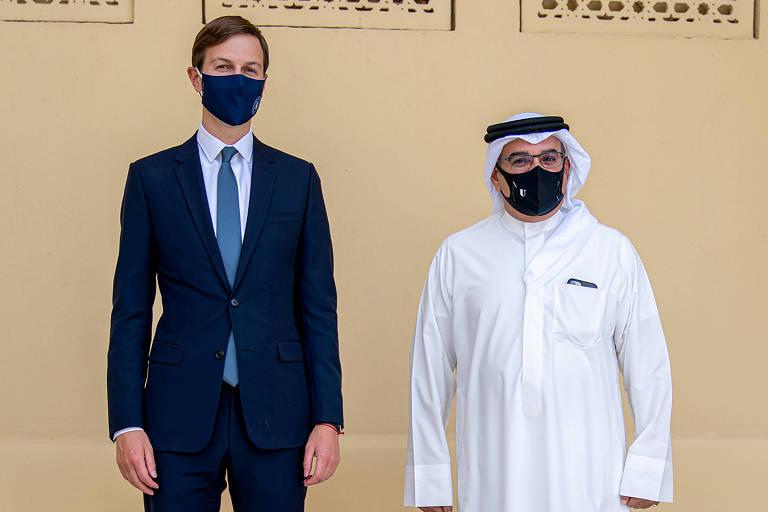 De terno e máscara, Kushner posa ao lado do príncipe, em kehfir tradicional árabe