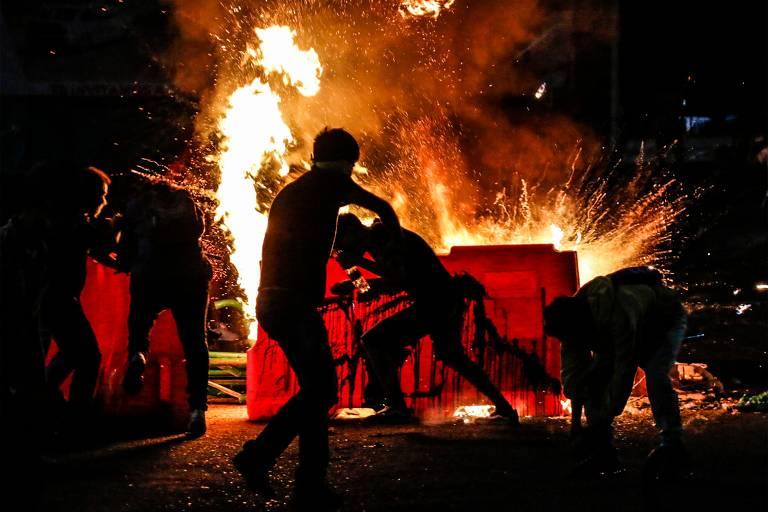 Manifestantes colocam fogo em barricada durante protesto contra a violência policial em Cucuta, próxima à fronteira com a Venezuela