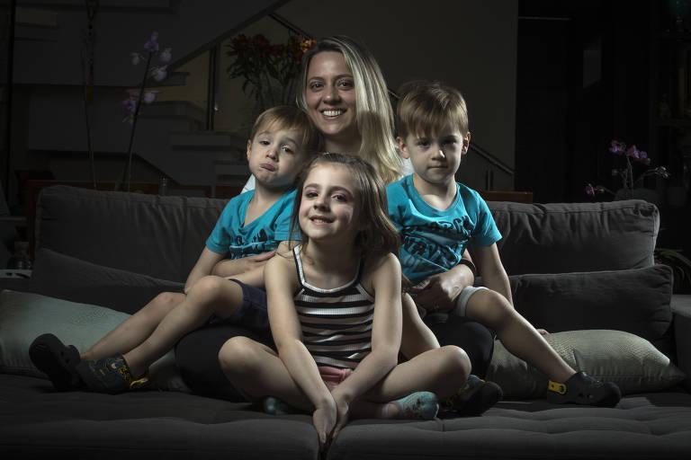 Mulher loira com duas crianças pequenas gêmeas e mais uma menina um pouco mais velha, sentados em sofá, sorrindo