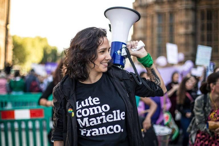 """Monica Benício, viúva de Marielle Franco, segura um megafone e veste uma camiseta com os dizeres """"Lute como Marielle Franco"""""""