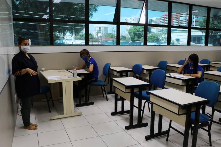 Professora com máscara, em pé, e alunos sentados em carteiras, espalhados