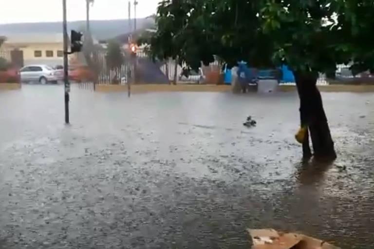 Praça tomada pela água turva, que encobre parte de uma árvore