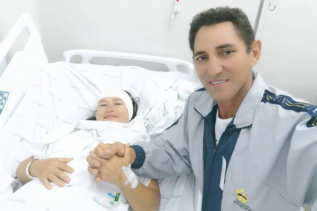 Mulher com faixa rodeando a cabeça acima dos olhos, deitada em cama de hospital, ela sorri e está de mão dadas com homem de pé que também sorri