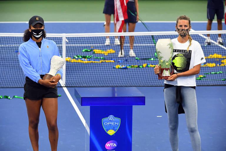 Osaka e Azarenka, ambas de máscara, segurando troféus