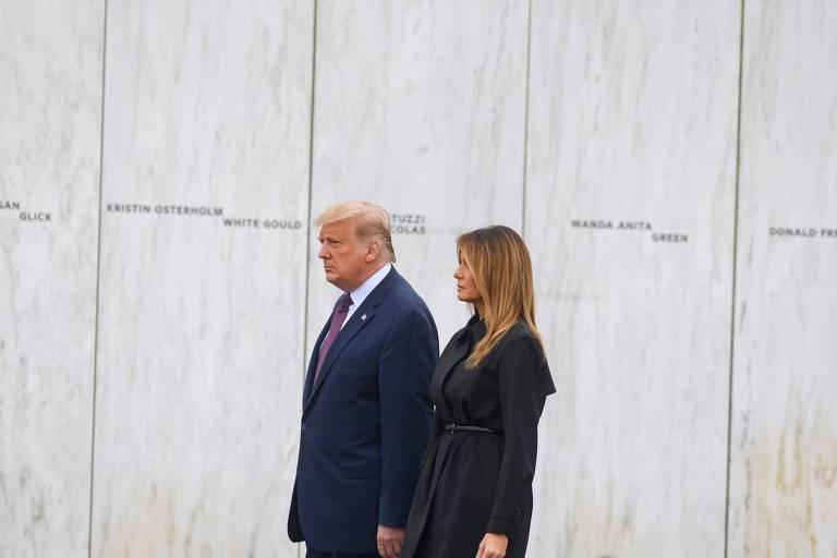Com fundo de mármore branco do memorial, Trump e Melania estão em pé