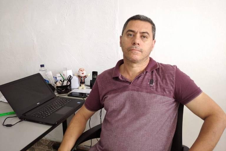 O corretor de imóveis Luciano Aparecido da Conceição está sentado em frente a uma mesa com um notebook aberto. Ele está sério.