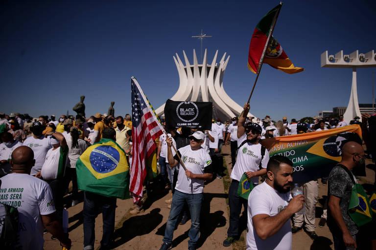 Protesto Pró Armas na Esplanada dos Ministérios; vemos um grande grupo de pessoas com bandeiras do Brasil, dos EUA e outras, aparentemente todos homens, em frente à Catedral de Brasília