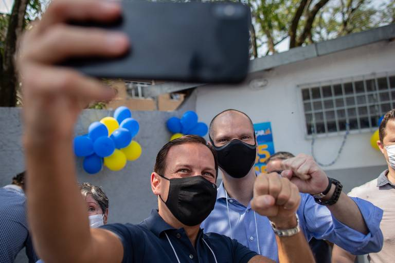 Governador tira selfie com Covas; ambos têm o braço esquerdo levantado e a mão fechada