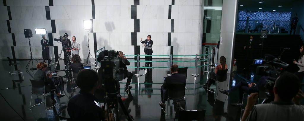 O presidente da Câmara, Rodrigo Maia, segue o novo protocolo sanitário em entrevista coletiva: repórteres ficam afastados e sentados em cadeiras distanciadas uma da outra