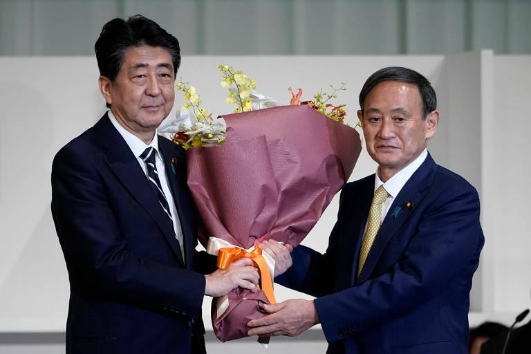 Dois homens de terno seguram buquê de flores