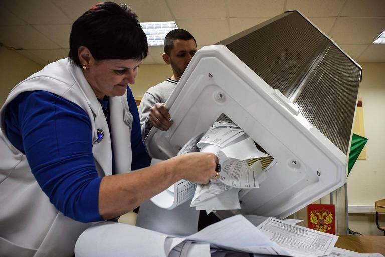 Funcionários de seção eleitoral esvaziam urna em ponto de votação de Novosibirsk, na Sibéria