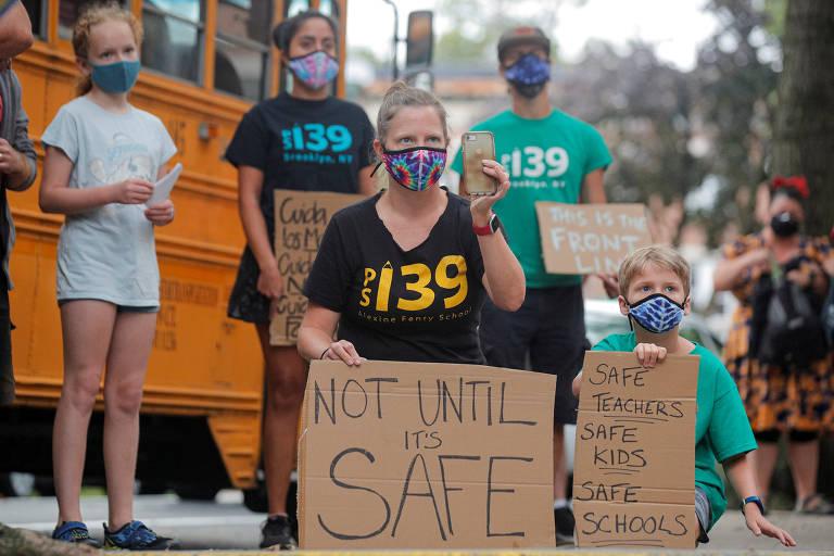 De máscara, mulher segura cartaz pedindo que reabertura ocorre com segurança; crianças , igualmente com proteção,também exibem cartazes