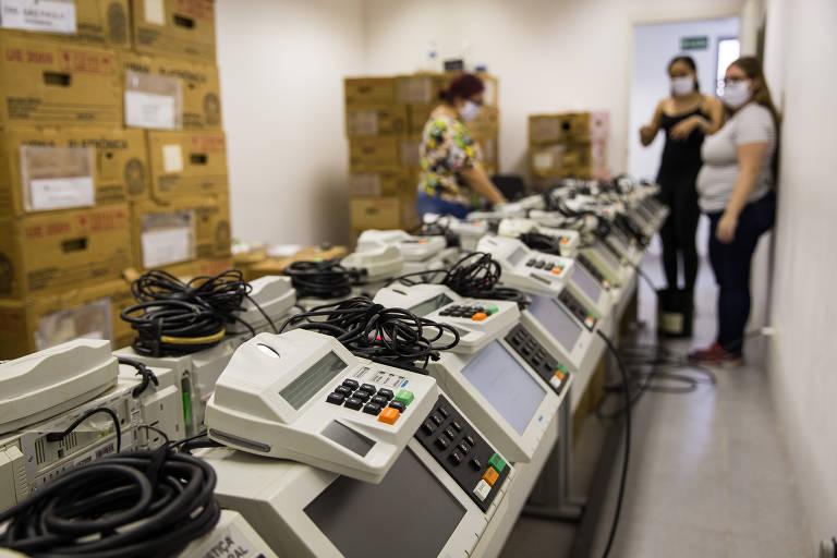 Com máscaras, funcionários ajustam urnas para as eleições municipais