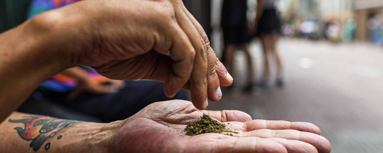 Mãos de um homem branco seguram uma pequena quantidade de flor de maconha diante de uma rua no fundo, desfocada