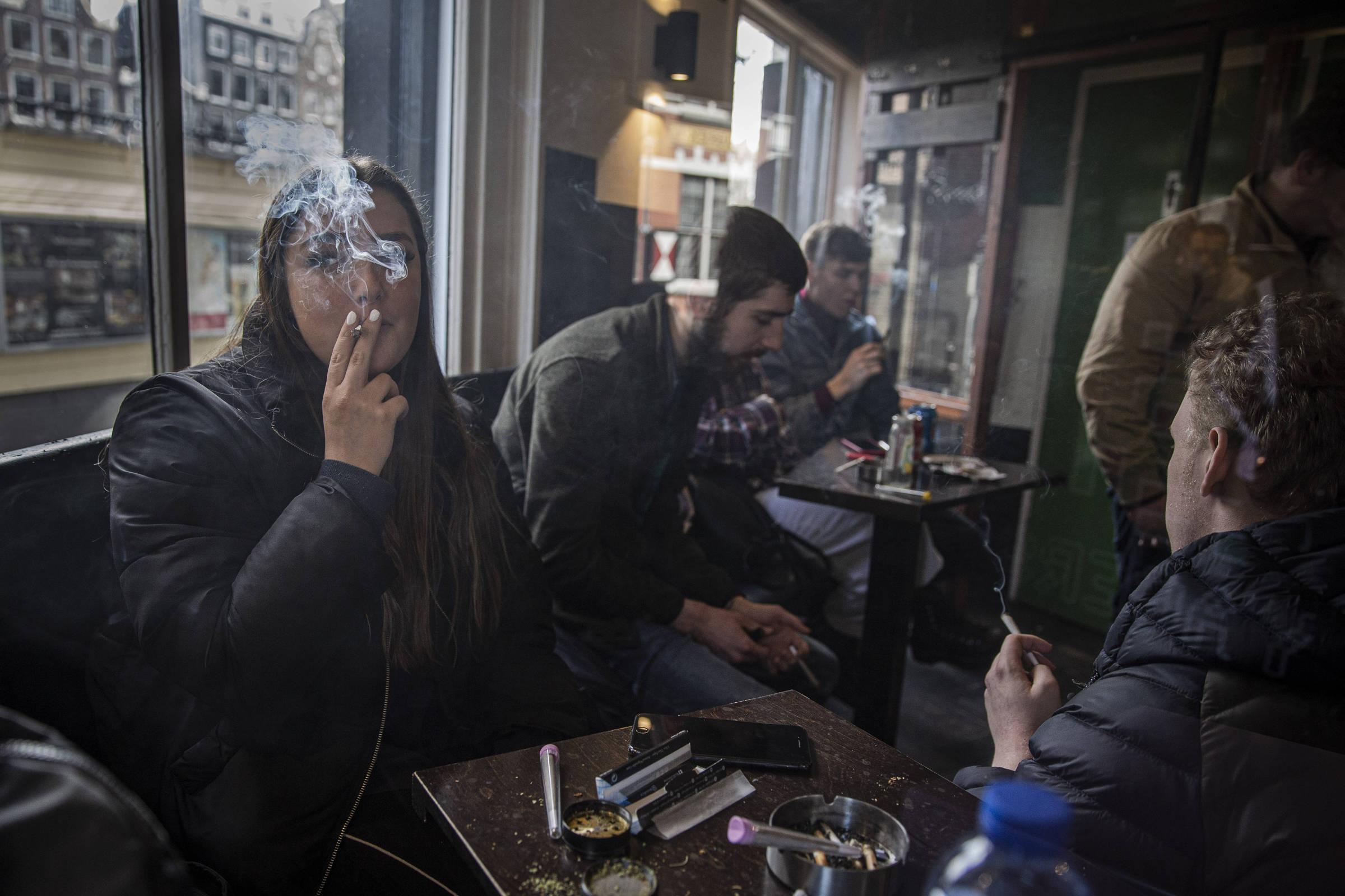 Jovens fumam maconha no centro de Amsterdã (acima) e no cofffeeshop Voyagers
