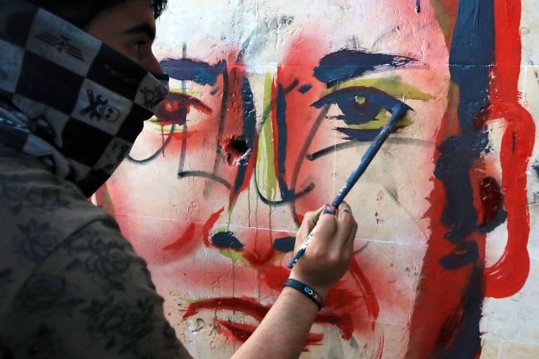 Em Bogotá, a capital da Colômbia, homem pinta em muro o rosto de Javier Ordoñez, morto pela polícia e transformado em símbolo da brutalidade policial no país sul-americano