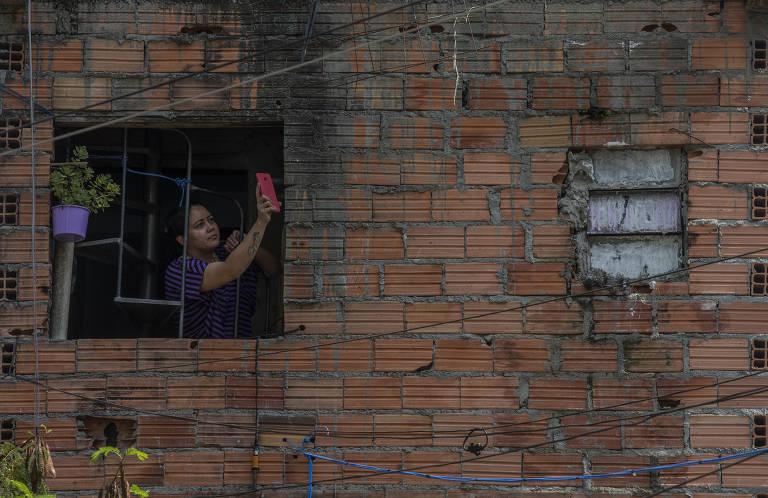 Maria de Fátima Bezerra Rodrigues tenta acessar a rede de internet de vizinhos em Heliópolis, onde vive em São Paulo. O bairro deve receber pontos de wifi livre a partir do projeto Mães da Favela ON, da Central Única das Favelas