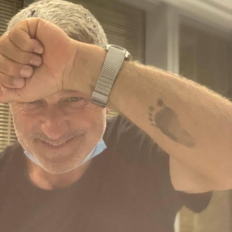 Alec Baldwin tatua pezinho do filho