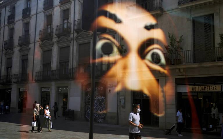 Vitrine de uma loja reflete uma máscara que se assemelha ao V de Vingança enquanto pessoas passam pela rua no Bairro Gótico, em Barcelona
