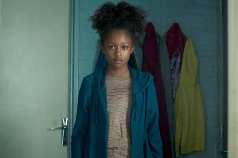 menina negra de casaco azul parada com cara de assustada